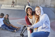 Portrait smiling teenage girls with BMX bicycle at skate park - CAIF05938