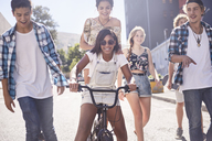 Teenage friends with BMX bicycle on sunny urban street - CAIF05944