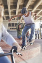 Friends watching teenage boy skateboarding at skate park - CAIF05956