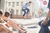 Friends watching teenage boy jumping skateboard at sunny urban corner - CAIF05971