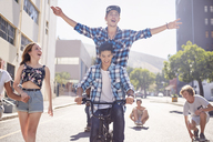Teenage friends riding BMX bicycle and skateboarding on sunny urban street - CAIF05977