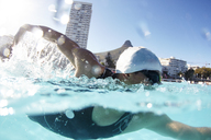 Male swimmer athlete swimming in sunny swimming pool - CAIF06010