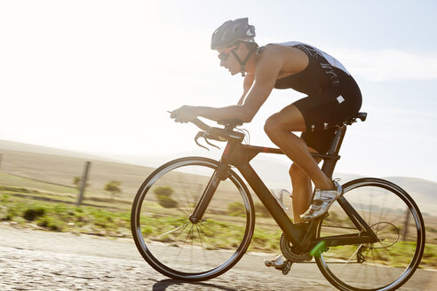 Male triathlete cyclist cycling on sunny rural road at sunrise - CAIF06013
