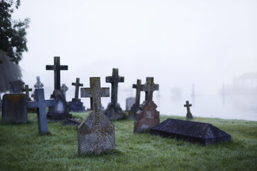 Crosses on gravestones in ethereal foggy cemetery - CAIF06028