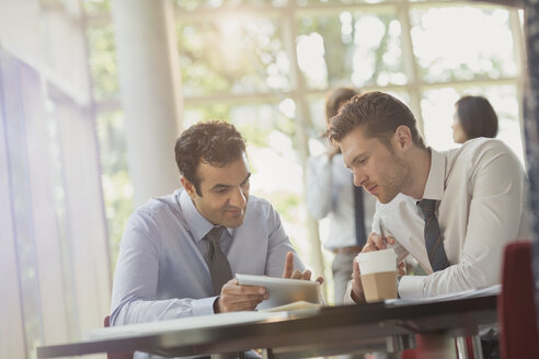 Businessmen using digital tablet at office table - CAIF06040