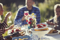 Family enjoying strawberry cake at sunny garden party patio table - CAIF06061