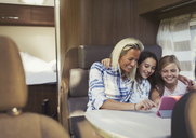 Smiling mother and daughters using digital tablet inside motor home - CAIF06070