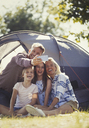 Happy family taking selfie with camera phone outside sunny campsite tent - CAIF06073