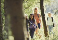 Mother and daughters hiking in sunny woods - CAIF06076