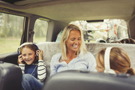 Laughing mother and daughters with headphones in back seat of car - CAIF06082