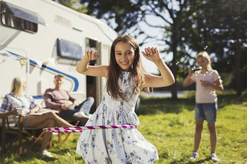 Portrait smiling girl spinning in plastic hoop outside sunny motor home - CAIF06091
