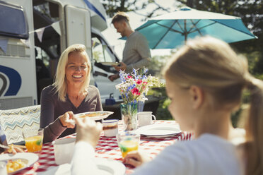 Smiling mother and daughter enjoying breakfast at table outside sunny motor home - CAIF06103
