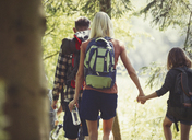 Mother and daughter with backpacks holding hands hiking in woods - CAIF06106