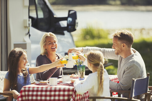Family toasting coffee and orange juice glasses at table outside sunny motor home - CAIF06109