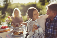 Affectionate father and daughter enjoying sunny garden party - CAIF06115