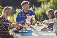 Family eating at sunny garden party patio table - CAIF06124