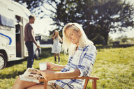Woman reading magazine and drinking coffee outside sunny motor home - CAIF06127