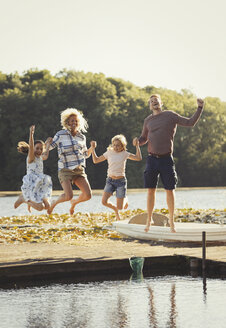 Portrait playful family jumping on sunny lake dock - CAIF06130