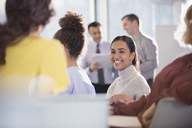 Smiling businesswoman talking to colleagues in conference audience - CAIF06193