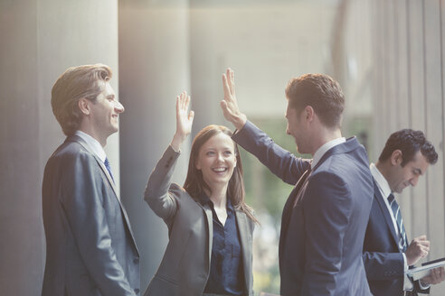 Business people high-fiving in office lobby - CAIF06205