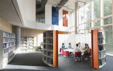 Business people meeting at round table in open plan library - CAIF06220
