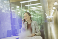 Smiling businesswoman talking on cell phone in conference room - CAIF06223