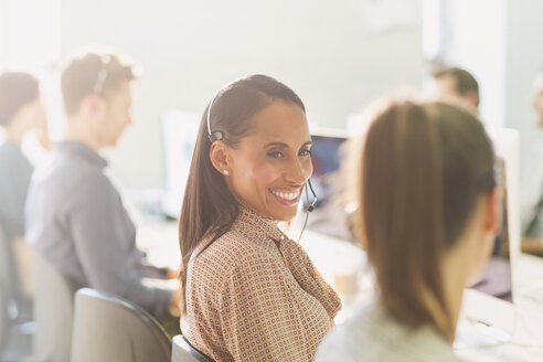 Smiling female telemarketers wearing headsets talking in sunny office - CAIF06226