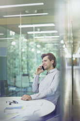 Businessman talking on cell phone in conference room - CAIF06235