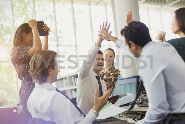 Business people high-fiving and celebrating in office - CAIF06241