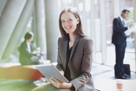 Portrait smiling businesswoman using digital tablet in sunny office lobby - CAIF06253