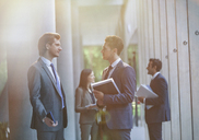 Businessmen talking in office lobby - CAIF06256
