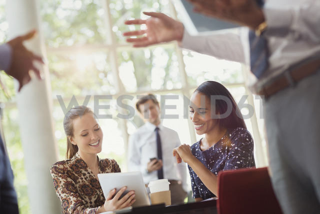 Businesswomen using digital tablet in office meeting - CAIF06259