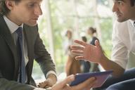Businessmen with digital tablet talking - CAIF06265