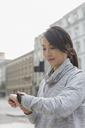 Female runner checking smart watch on urban street - CAIF06313