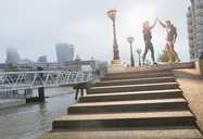 Runners high-fiving on sunny urban steps - CAIF06325