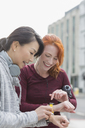 Smiling female runners checking smart watches on urban sidewalk - CAIF06337