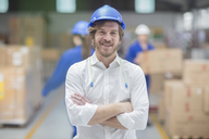 Portrait of smiling man wearing hard hat in factory - ZEF15118