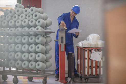 Man wearing hard hat checking delivery in factory - ZEF15136