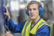 Portrait of man wearing ear defenders operating machine in factory - ZEF15142