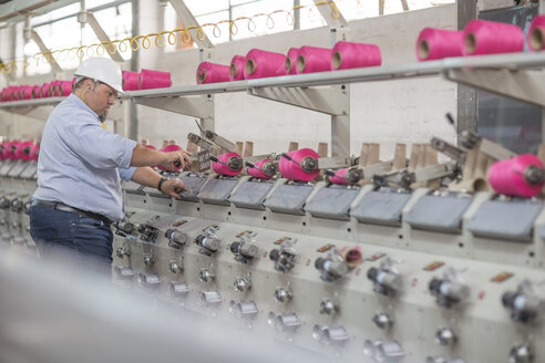 Man working with spools in factory - ZEF15154