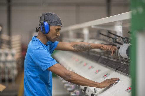 Man wearing ear defenders operating machine in factory - ZEF15157