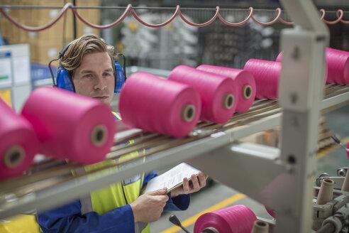 Man wearing ear defenders working at spool machine in factory - ZEF15160