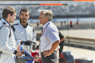 Manager and formula one race car drivers talking on sports track - CAIF06390