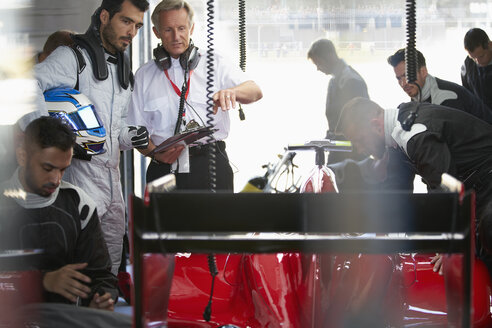 Manager and formula one driver watching pit crew working on race car in repair garage - CAIF06396