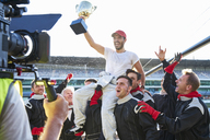 Racing team celebrating victory carrying race car driver with trophy on shoulders - CAIF06399