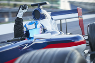 Portrait formula one race car driver wearing helmet and cheering with fist on sports track - CAIF06402