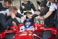 Manager and pit crew congratulating formula one race car driver - CAIF06408