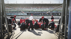 Manager and pit crew replacing tires on formula one race car in pit lane - CAIF06414