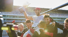 Formula one racing team carrying driver with trophy on shoulders, celebrating victory - CAIF06420