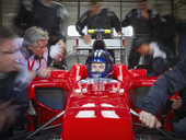 Pit crew working around serious formula one race car driver - CAIF06459